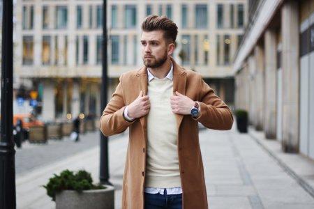 Brązowe sztyblety i beżowy płaszcz